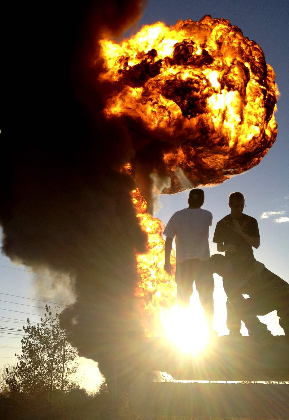Onlookers watch a fireball rise from Speedway International, a company that was storing biofuel.  Provincial investigators pegged spontaneous combustion as the cause of the fire. 