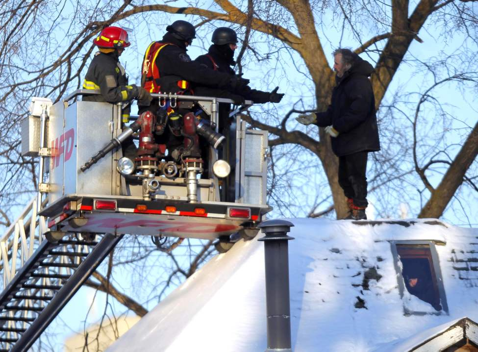 Police and fire fighters try to talk down Ed Ackerman from the roof of his to-be-demolished home. Ackerman was fighting a City demolition order. The situation was resolved peacefully. January 24, 2012 (BORIS MINKEVICH / WINNIPEG FREE PRESS)