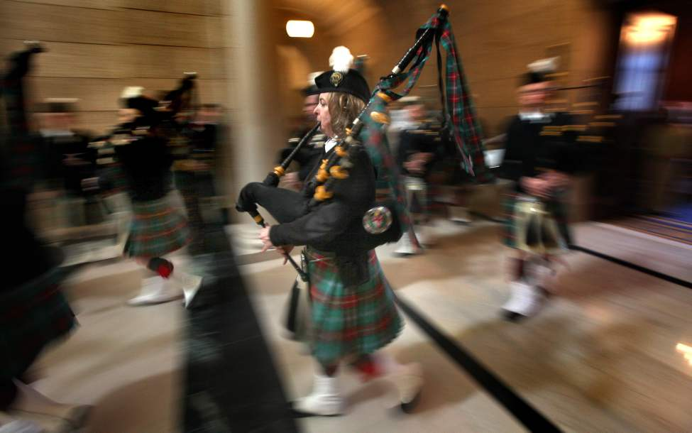 The Pipes and Drums of Manitoba lead costumed Scots in a parade around the Manitoba Legislative Building Thursday afternoon to mark