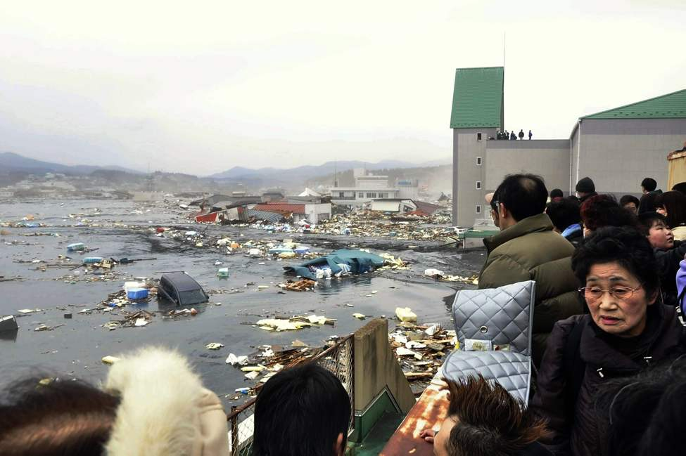 People watch the aftermath of tsunami tidal waves covering a port at Kesennuma in Miyagi Prefecture, northern Japan, after strong earthquakes hit the area Friday, March 11, 2011. (AP Photo/Keichi Nakane, The Yomiuri Shimbun)