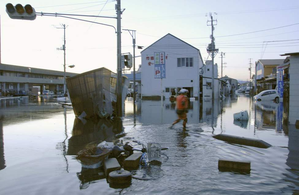 A man wades through a flooded street after tsunami spawned by a powerful earthquake in Iwaki, Fukushima prefecture (state), Japan, Friday, March 11, 2011.  The largest earthquake in Japan's recorded history slammed the eastern coast Friday. (AP Photo/Kyodo News)