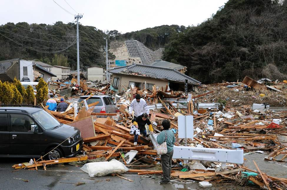 Residents walk through the rubles of residents collapsed by a powerful earthquake in Iwaki, Fukushima prefecture (state), Japan, Friday, March 11, 2011. The largest earthquake in Japan's recorded history slammed the eastern coast Friday. (AP Photo/Kyodo News)