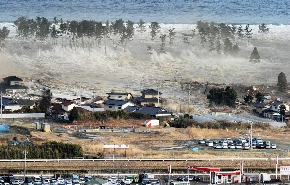 Waves of tsunami hit residences after a powerful earthquake in Natori, Miyagi prefecture (state), Japan, Friday, March 11, 2011.  The largest earthquake in Japan's recorded history slammed the eastern coast Friday. (AP Photo/Kyodo News)