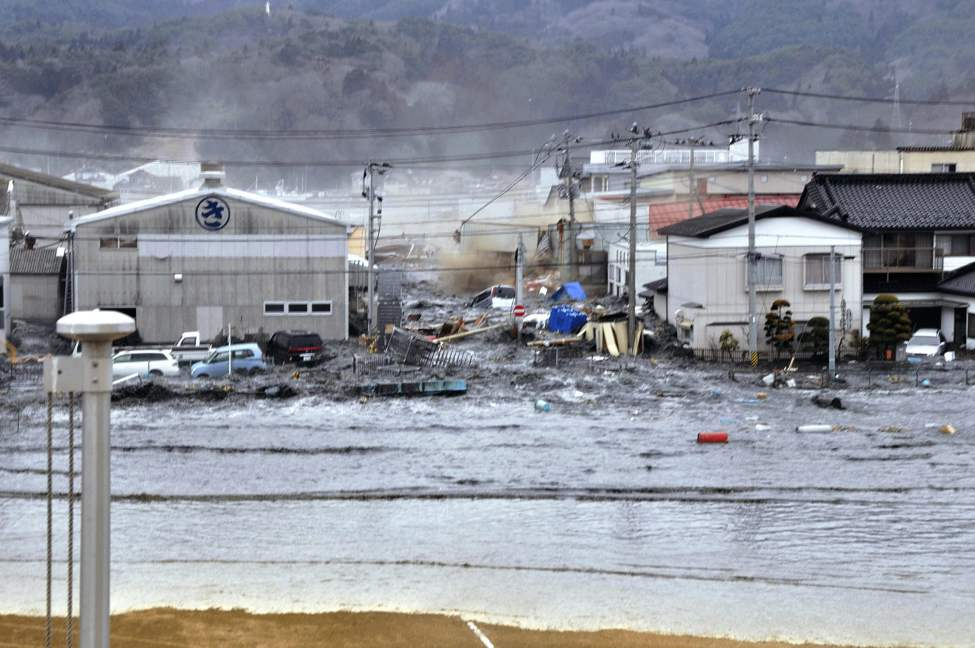 A tsunami tidal wave washes away houses in Kesennuma, Miyagi Prefecture, Friday, March 11, 2011 after strong earthquakes hit the area. (AP Photo/Keichi Nakane, The Yomiuri Shimbun)