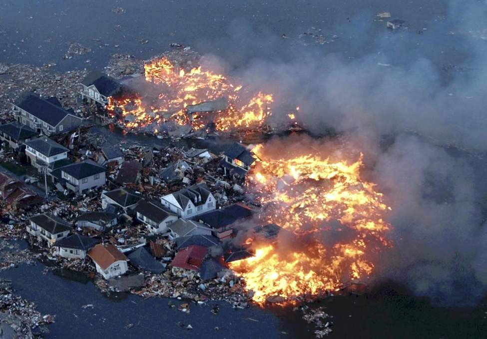 Houses are in flame while the Natori river is flooded over the surrounding area by tsunami tidal waves in Natori city, Miyagi Prefecture, northern Japan, March 11, 2011, after strong earthquakes hit the area. (AP Photo/Yasushi Kanno, The Yomiuri Shimbun)