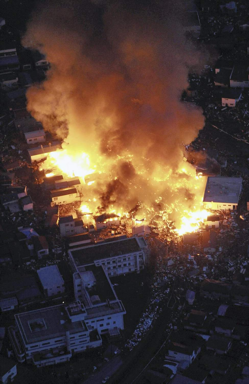 Flames rise from houses on fire after powerful earthquakes hit Yamada, Iwate Prefecture, northern Japan, Friday, March 11, 2011. (AP Photo/Osamu Kanazawa, The Yomiuri Shimbun)