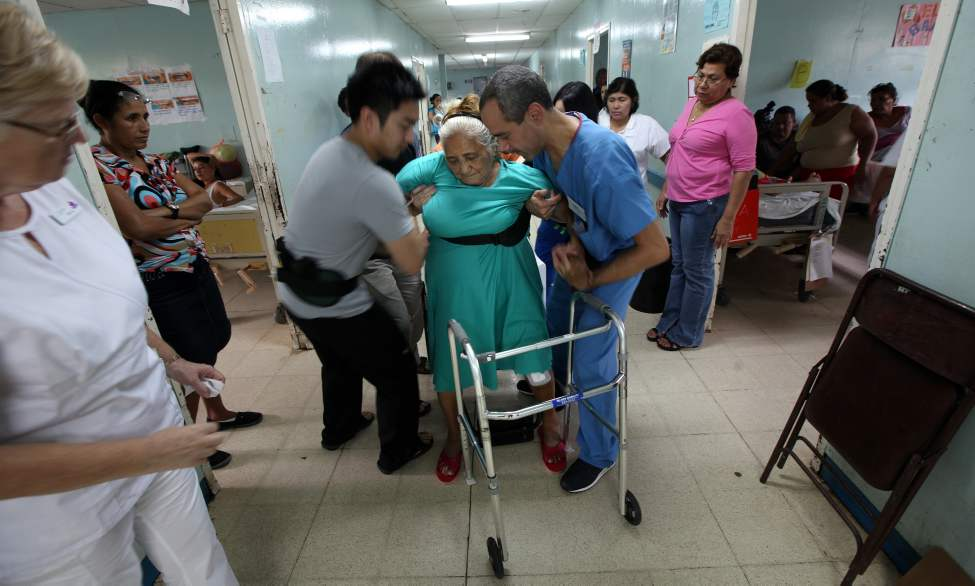 MANAGUA - Lucia Moyorga is supported by Adian Salonga, left, and Victor Medina as she gets to her feet for the first time following surgery.