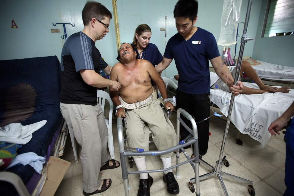 MANAGUA - The morning following his surgery, Juan Canda grimaces as he sinks into a chair after his first walk with physiotherapists Ian WIndle, left, and Adrian Salonga. Juan received bilateral surgery.