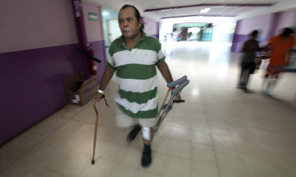 MANAGUA - Using a single cane and carrying his crutches, Canda leaves Hospital Escuela for home four days after bilateral surgery.