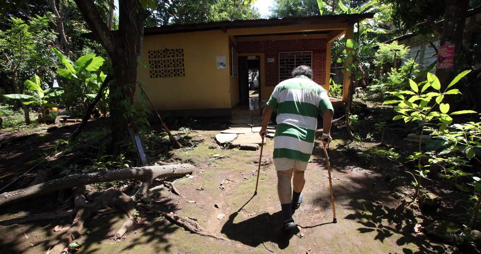 MANAGUA - Canada walks to his home on the outskirts of Managua four days after receiving bilateral knee replacement surgery.