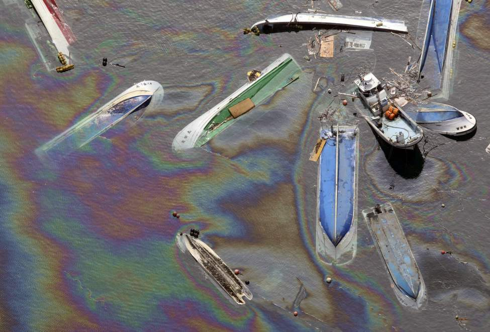 Vessels float on oil spilled water in Fudai, Iwate, northern Japan Monday, March 14, 2011 following Friday's massive earthquake and the ensuing tsunami. (AP Photo/Yomiuri Shimbun, Hiroshi Adachi)