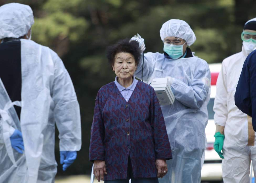 Residents evacuated from areas surrounding the Fukushima nuclear facilities damaged in Friday's massive earthquake, are checked for radiation contamination, Sunday, March 13, 2011, in Koriyama city, Fukushima prefecture, Japan. (AP Photo/Wally Santana)