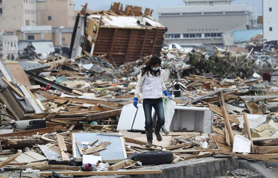 """A woman looks for her father-in-law's """"ihai"""" spirit tablet, a placard to designate his seat in a house, in Ofunato, northern Japan, Monday, March 14, 2011, three days after a powerful earthquake-triggered tsunami hit the country's east coast. (AP Photo/The Yomiuri Shimbun, Masamichi Genko)"""