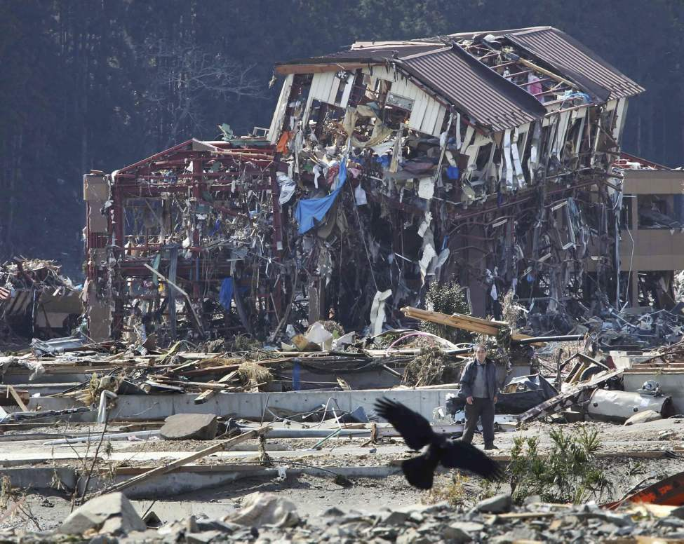 A bird flies in front of damaged buildings in Minamisanriku town, Miyagi Prefecture, northern Japan, Monday, March 14, 2011, three days after a powerful earthquake-triggered tsunami hit the country's east coast. (AP Photo/The Yomiuri Shimbun, Hiroaki Ono)