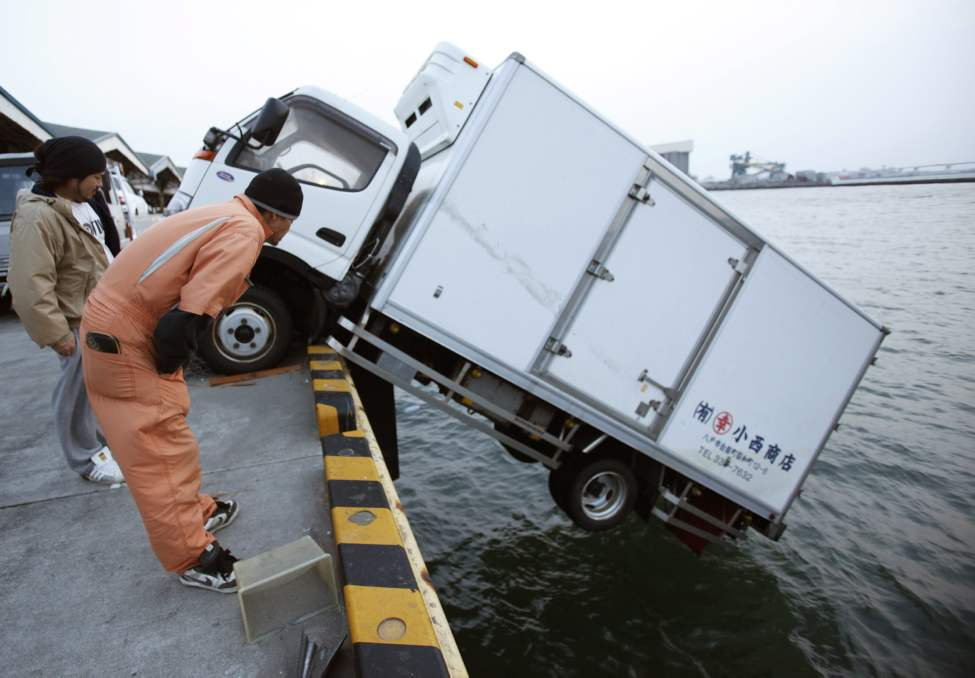 People look at a truck that dangles on the edge of a pier in Hachinohe, Aomori Prefecture, northern Japan, Monday, March 14, 2011, three days after a powerful earthquake-triggered tsunami hit Japan's east coast. (AP Photo/Shizuo Kambayashi)