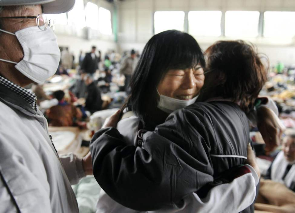 Relatives react as they reunite at each other at a shelter in Kesennuma, Miyagi Prefecture, Monday March 14, 2011, three days after northeastern coastal towns were devastated by an earthquake and tsunami. (AP Photo/Kyodo News)
