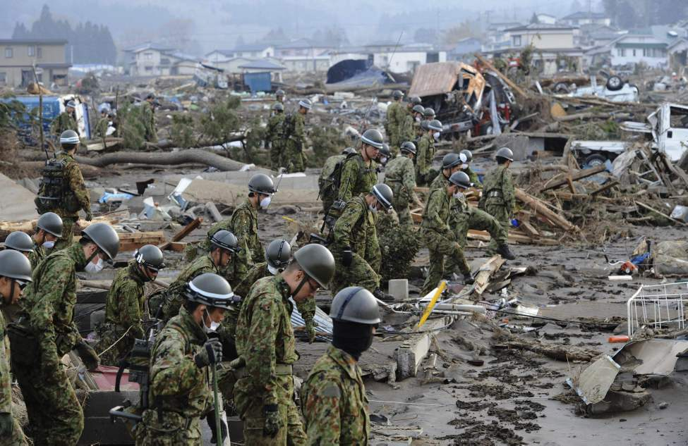 Self-Defense Force members inspects the devastated area before they use heavy machinery in Noda village, northern Japan, Monday, March 14, 2011, three days after a powerful earthquake-triggered tsunami hit the country's east coast. (AP Photo/The Yomiuri Shimbun, Yoichi Hayashi)