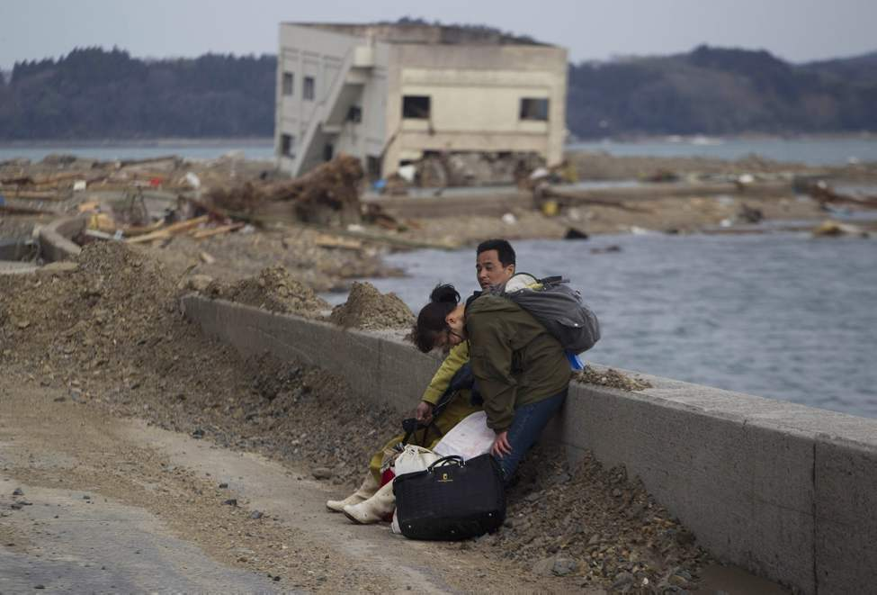 A Japanese couple stop to rest along a highway as they carry their belongings away form their destroyed village of Saito in northeastern Japan, Monday, March 14, 2011. Rescue workers used chain saws and hand picks Monday to dig out bodies in Japan's devastated coastal towns, as Asia's richest nation faced a mounting humanitarian, nuclear and economic crisis in the aftermath of a massive earthquake and tsunami that likely killed thousands. (AP Photo/David Guttenfelder)