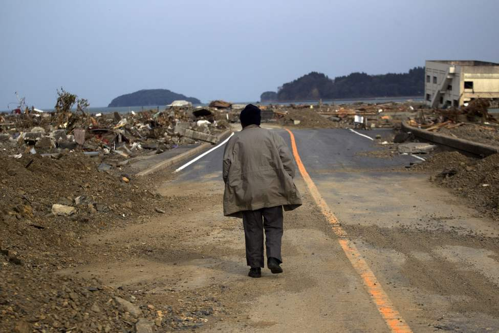 A Japanese earthquake and tsunami survivor walks alone on a road past the destroyed village of Saito, in northeastern Japan, Monday, March 14, 2011. (AP Photo/David Guttenfelder)