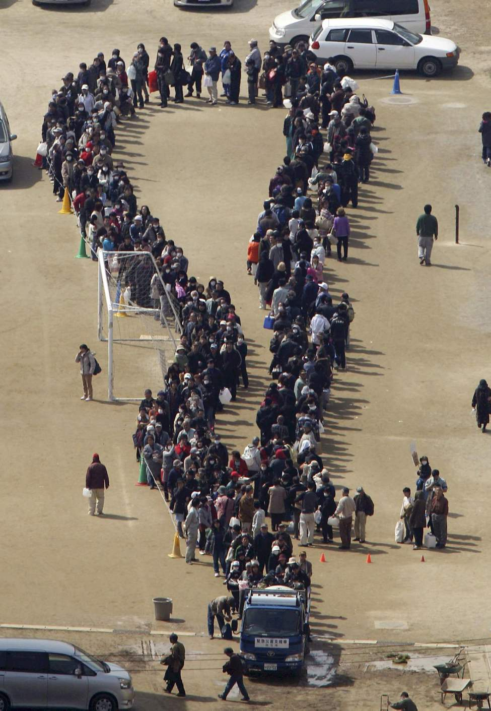 People line up to get kerosene in Hitachi in Ibaraki Prefecture (state) Monday, March 14, 2011, three days after a powerful earthquake-triggered tsunami hit the country's northeast coast. (AP Photo/The Yomiuri Shimbun, Kenichi Unaki)