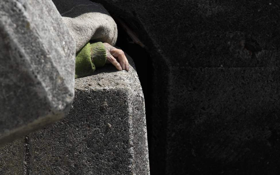 The hand of a man killed, sits among concrete sea barriers Monday, March 14, 2011, in Toyoma, northern Japan, three days after a giant quake and tsunami struck the country's northeastern coast. (AP Photo/Gregory Bull)