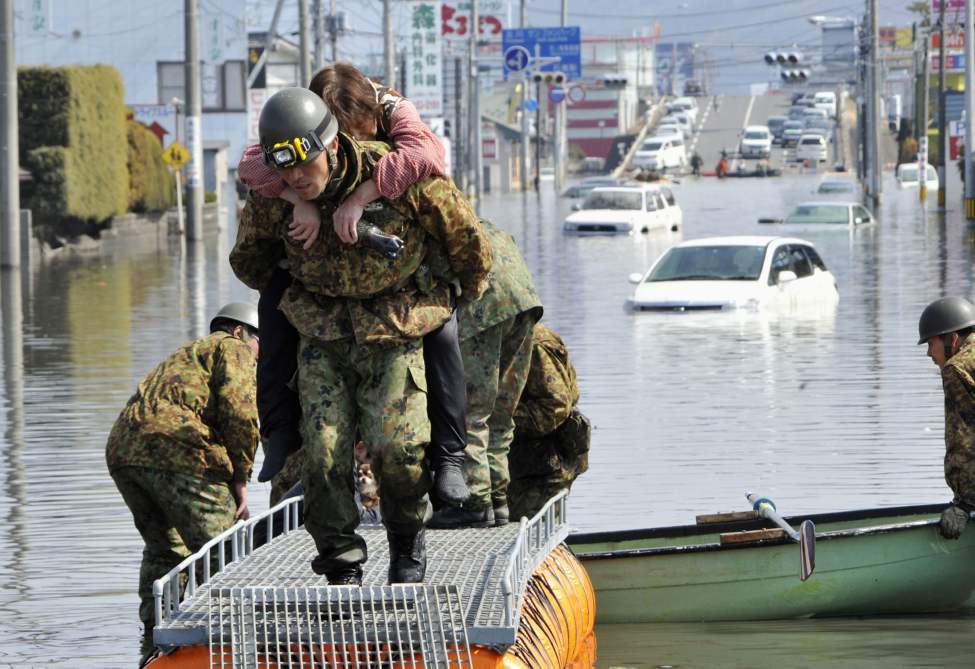 Soldiers of Japan Self Defense Forces rescue a tsunami victim from a flooded area in Ishinomaki, Miyagi Prefecture, Sunday, March 13, 2011. (AP Photo/Kyodo News)