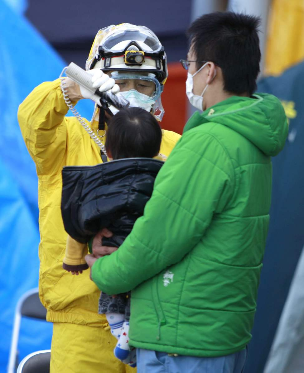 A child evacuated from areas surrounding the Fukushima nuclear facilities damaged in Friday's massive earthquake is checked for radiation exposure with other residents Sunday, March 13, 2011, in Koriyama city, Fukushima prefecture, Japan. (AP Photo/Wally Santana)