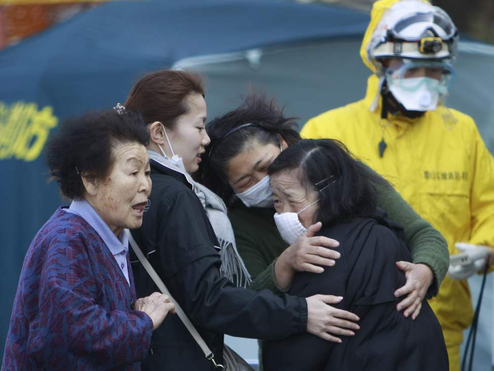 Residents evacuated from areas surrounding the Fukushima nuclear facilities damaged in Friday's massive earthquake react during a check for radiation contamination, Sunday, March 13, 2011, in Koriyama city, Fukushima prefecture, Japan. (AP Photo/Wally Santana)