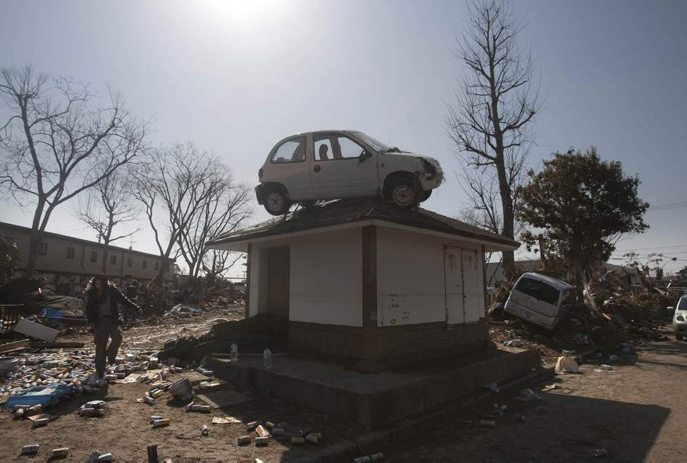 A car sits on top of a small building in a destroyed neighborhood in Sendai, Japan, on Sunday, March 13, 2011 after it was washed into the area by the tsunami that hit northeastern Japan.  (AP Photo/David Guttenfelder)