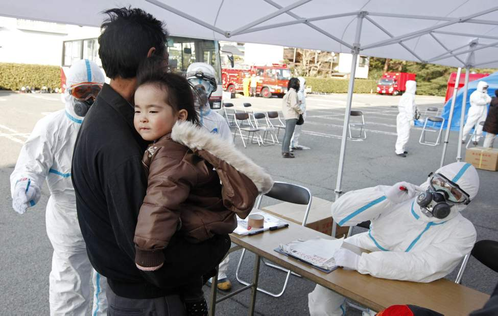 A man holds his baby as they are prepared to be scanned for levels of radiation in Koriyama, Fukushima Prefecture, Japan, Sunday, March 13, 2011. Friday's quake and tsunami damaged two nuclear reactors at a power plant in the prefecture, and at least one of them appeared to be going through a partial meltdown, raising fears of a radiation leak. (AP Photo/Mark Baker)