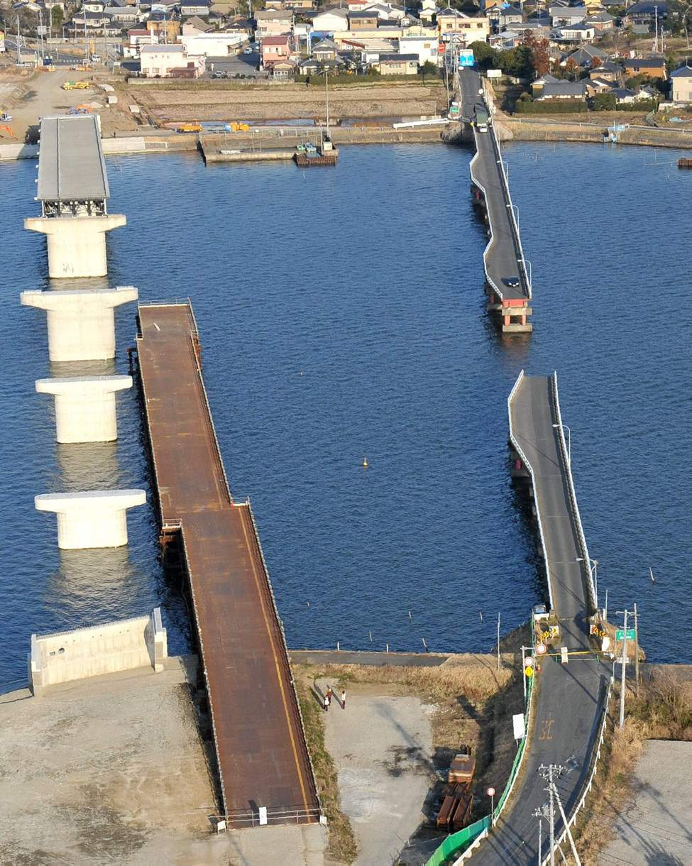 A bridge under construction, left, and another one are damaged in Namegata, Ibaraki prefecture, a day after one of Japan's strongest earthquakes ever recorded hit the country's east coast. (AP Photo/Kyodo News)