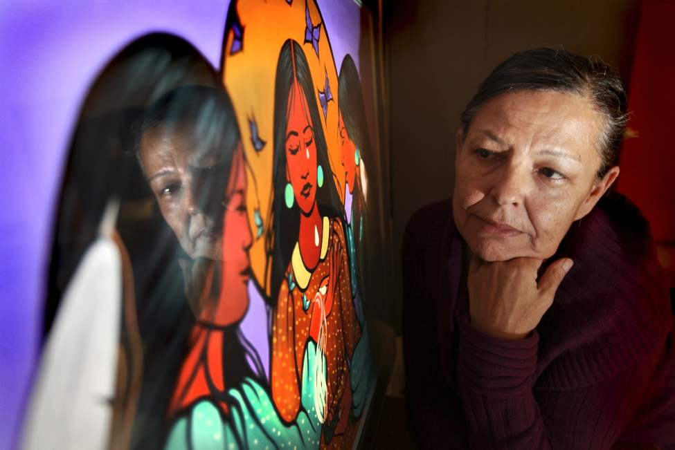 Portrait of Leslie Spillet is the executive director of Ka Ni Kanichihk, a community-based services centre. They developed a support program for families of missing and murdered women in Manitoba. Spillet sits next to a paiting by Jackie Traverse depicting a event honoring missing and murdered women called