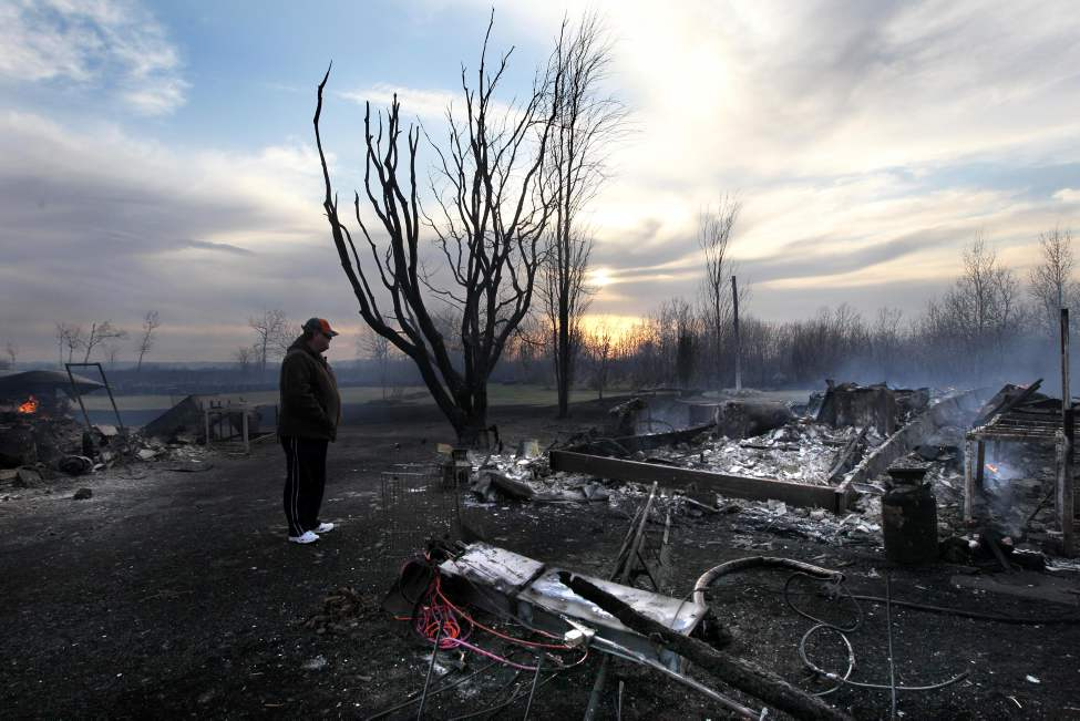 Werner Wersh, a neighbour to Lois  and Lorne Downey, surveys the piles of burning rubble which is all that remains of the  Downey's homestead near Teulon, Manitoba after a grass fire got out of control and burned down their house, barn, RV and work shop. April 06,  2012  (Ruth Bonneville/Winnipeg Free Press)