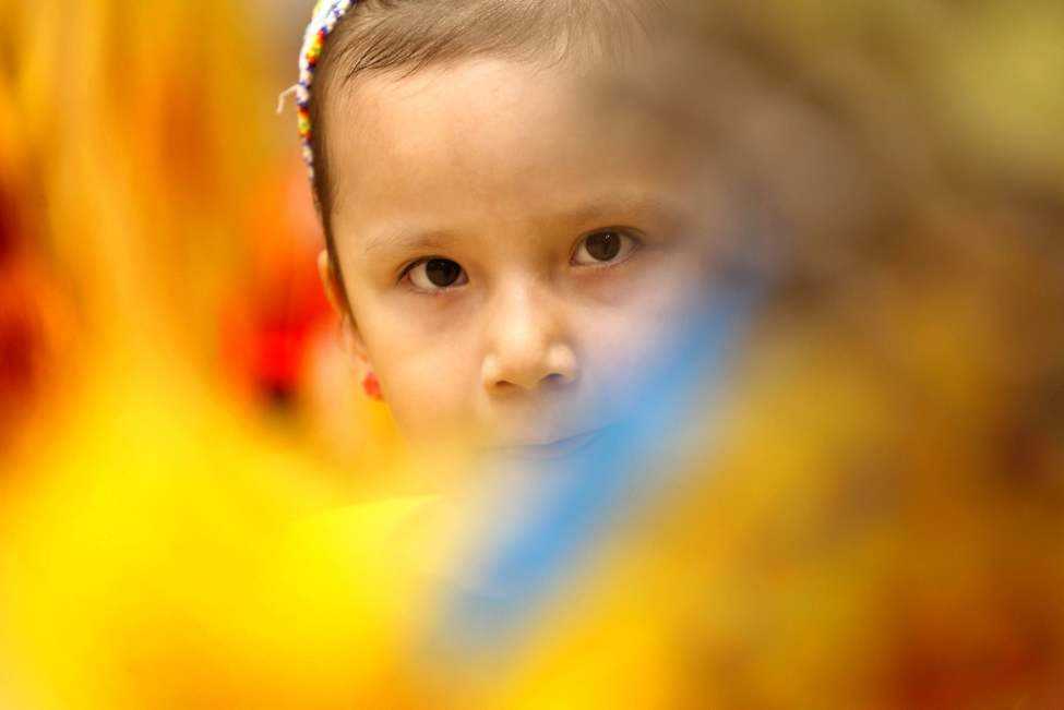 Four-year-old Serene Goodwill peers through her dad's feathers at The 23rd annual Traditional Graduation Pow Wow held at the Investors Group Athletic Centre Saturday. May 05,  2012 (Ruth Bonneville/Winnipeg Free Press)