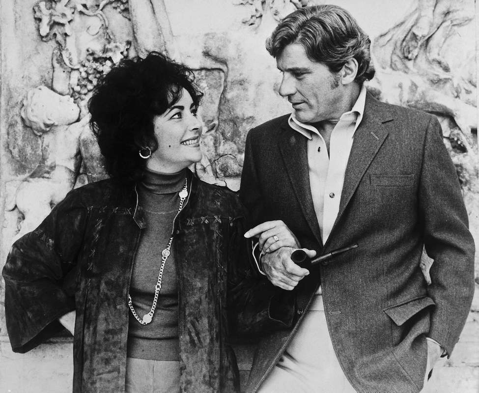 In this Oct. 9, 1976 file photo, British actress Elizabeth Taylor is seen with fiance John Warner, in Vienna, Austria, where Taylor is filming the screen version of 'A Little Night Music'. (AP Photo/HO, File)