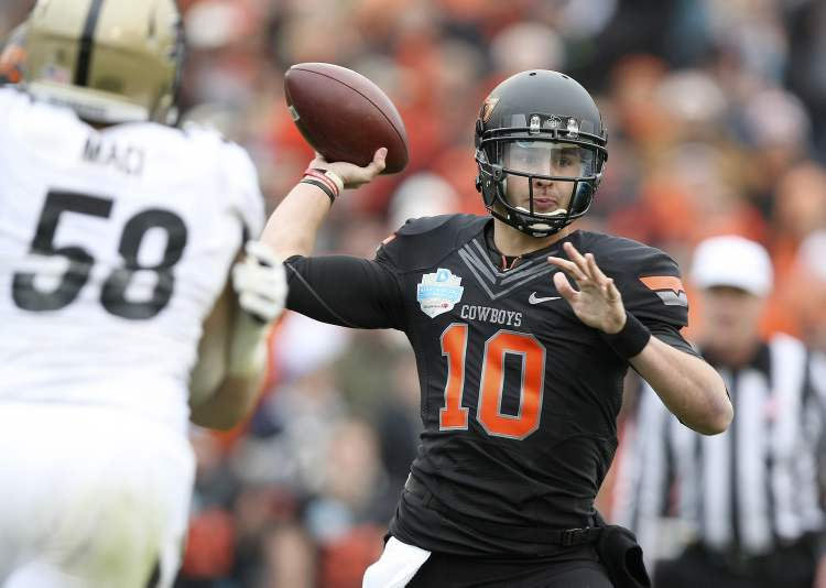 Oklahoma State Cowboys quarterback Clint Chelf (10) makes a pass against Purdue during the Heart of Dallas Bowl on Tuesday in Dallas. The Oklahoma State Cowboys defeated the Purdue Boilermakers, 58-14.