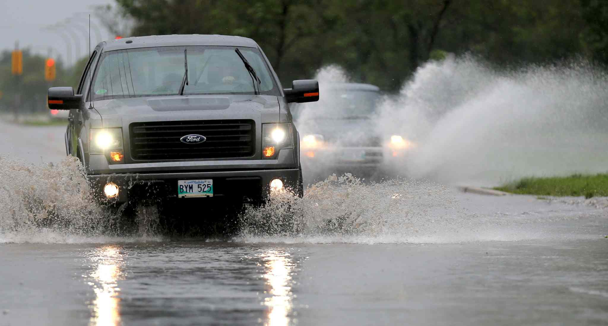 Vehicles splash through a deep puddle at Notre Dame Avenue and Border Street Sunday.