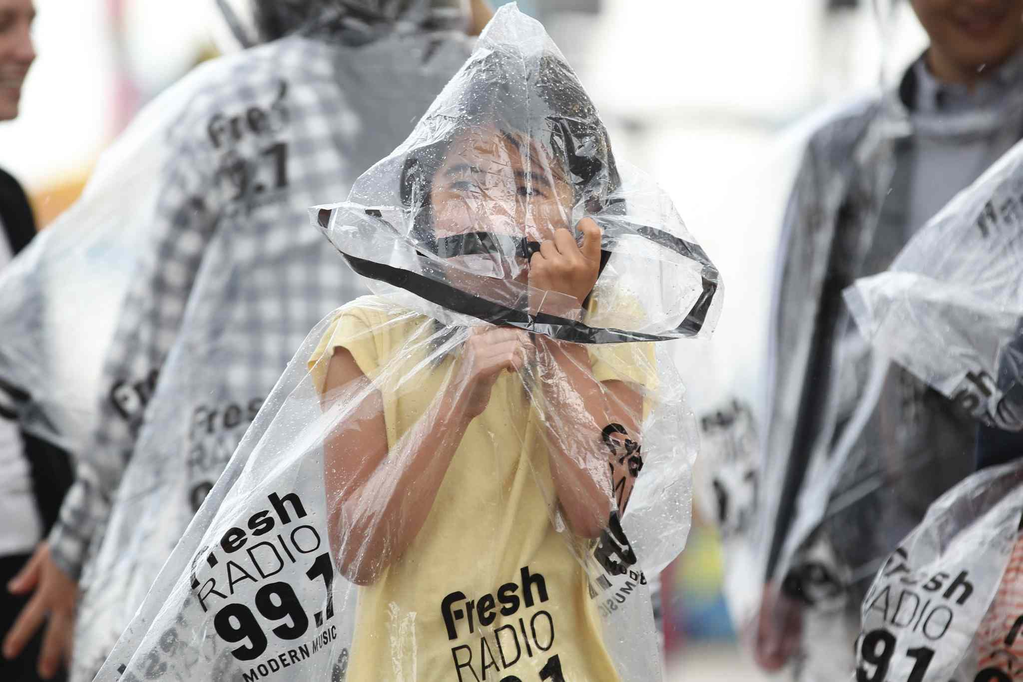 Eight-year-old Kanade Uesugi cover her face with a  hood on her plastic rain-gear him and his family wear to keep dry from the rain while attending the Red River Ex Wednesday evening.