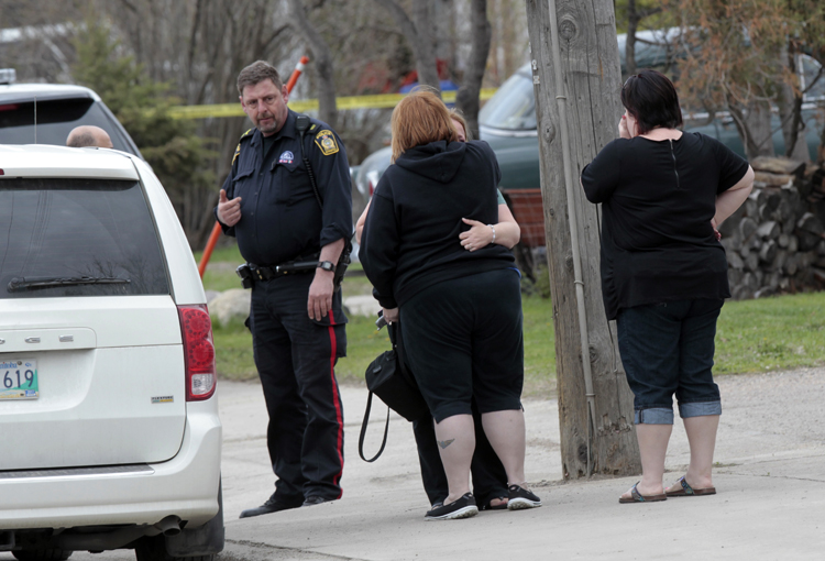 Women being comforted outside the home on Roblin Boulevard.
