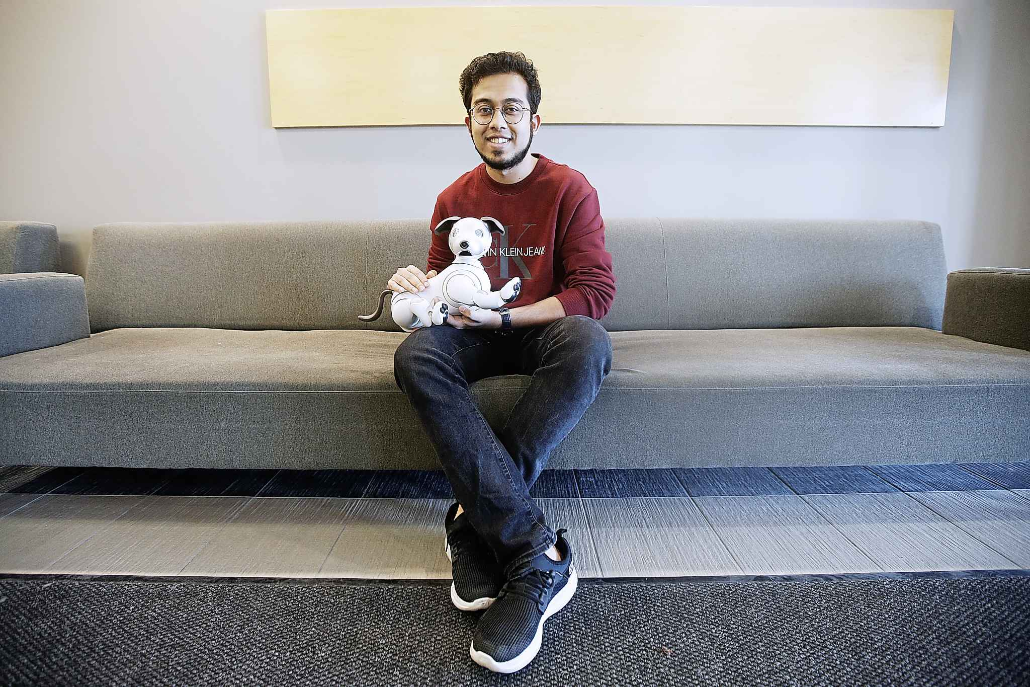 Rahatul Ananto, co-investigator in a U of M computer science study, with an AIBO robot. Ananto is a masters student in the Human Robotics Interaction program in the department of Computer Science and is looking for lonely people to live with the robot for 8 weeks.