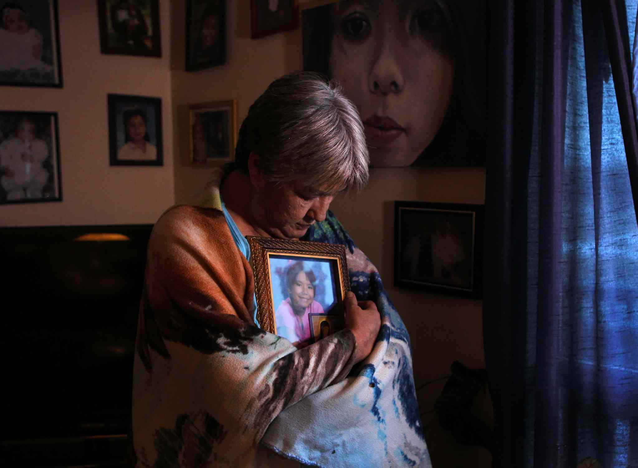Tina Fontaine's Great Aunt, Thelma Favel holds back tears as she wraps herself in a blanket and hugs a photo of Tina next to a window in her home in Sagkeeng First Nation on Dec. 11.  Next to her is a wall of photos of Tina with family members as well as a painting of Tina sent to her by a stranger. (Ruth Bonneville / Winnipeg Free Press)