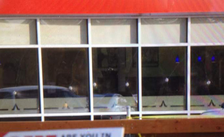 Bullet holes are seen in the window of the Salisbury House restaurant.