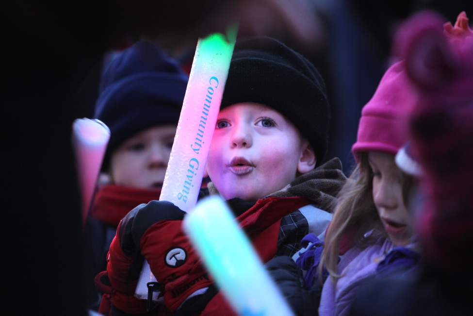 Three-year-old Linden Farrant waves his glow stick while watching the parade with friends. (Ruth Bonneville/Winnipeg Free Press)