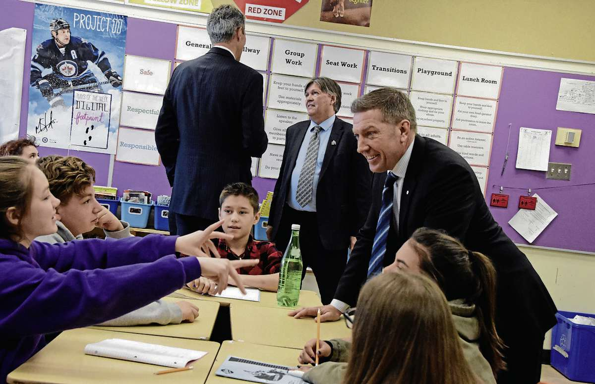 Above, former NHLer Sheldon Kennedy chats with kids in Meghan McOmber's Grade 7 class at Bernie Wolfe Community School (95 Bournais Dr.), with Premier Brian Pallister and education minister Ian Wishart in the background.