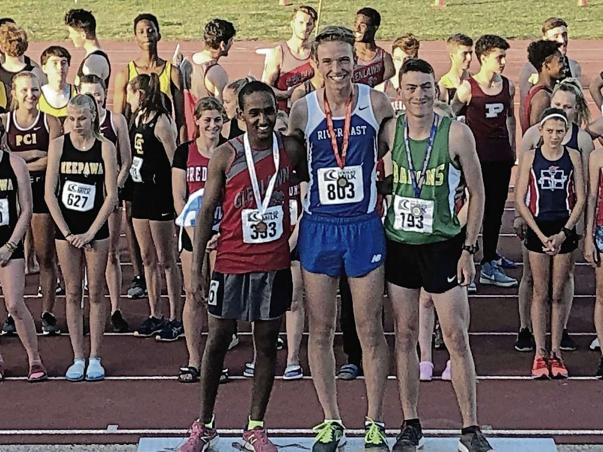 River East's Calvin Reimer (centre) placed first in the boys varsity 1,500-metre run at the provincial high school track meet on June 6. Reimer also placed third in the boys varsity 3,000-metre race.