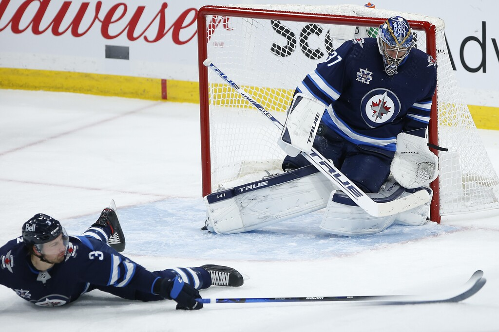 Connor Hellebuyck and Tucker Poolman can't stop the shot from Ottawa's Tim Stutzle as he scores his second goal of the game during the third period. (John Woods / The Canadian Press)