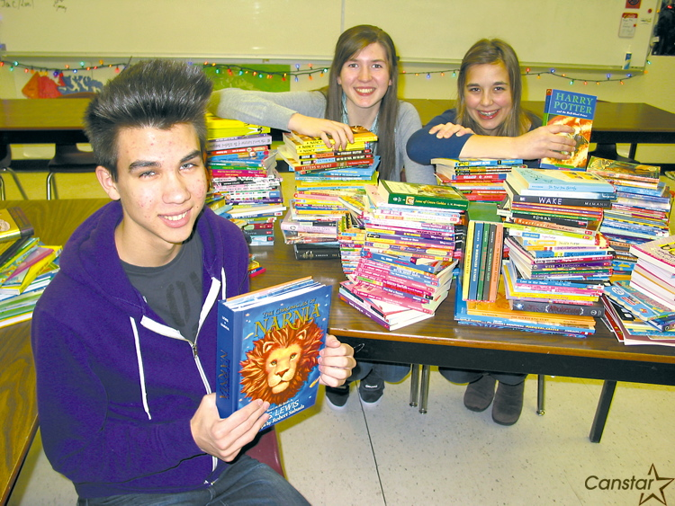 From left to right: Ian Hay, Jamie Campbell and Julia Stoyko with some of the thousands of books collected at J. H. Bruns Collegiate recently.