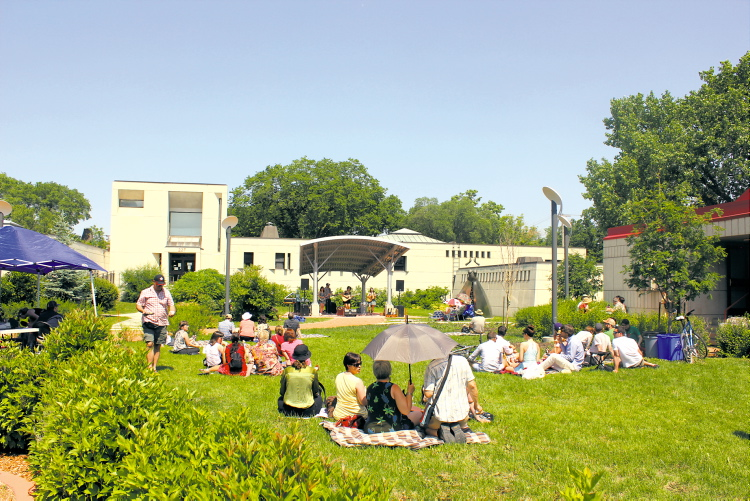 Visitors to the free lunchtime concert grabbed hats, chairs, blankets — and even umbrellas — to help keep cool and comfortable in the midday sun.  (PHOTO COURTESY OF FESTIVAL DU VOYAGEUR)