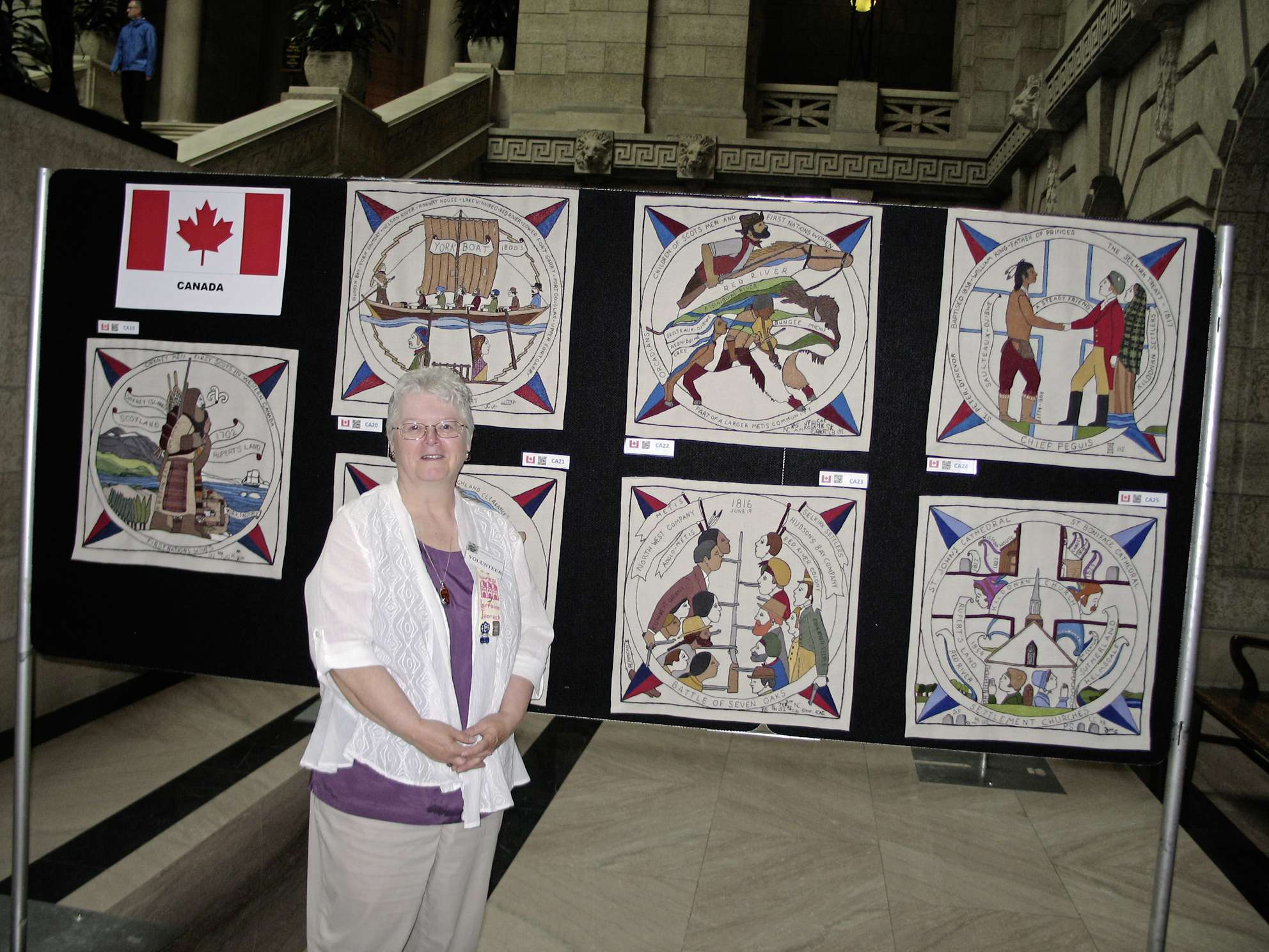 Lorraine Iverach pictured in front of the seven panels of the Scottish Diaspora Tapestry that depict Manitoba. Iverach worked on five of them.