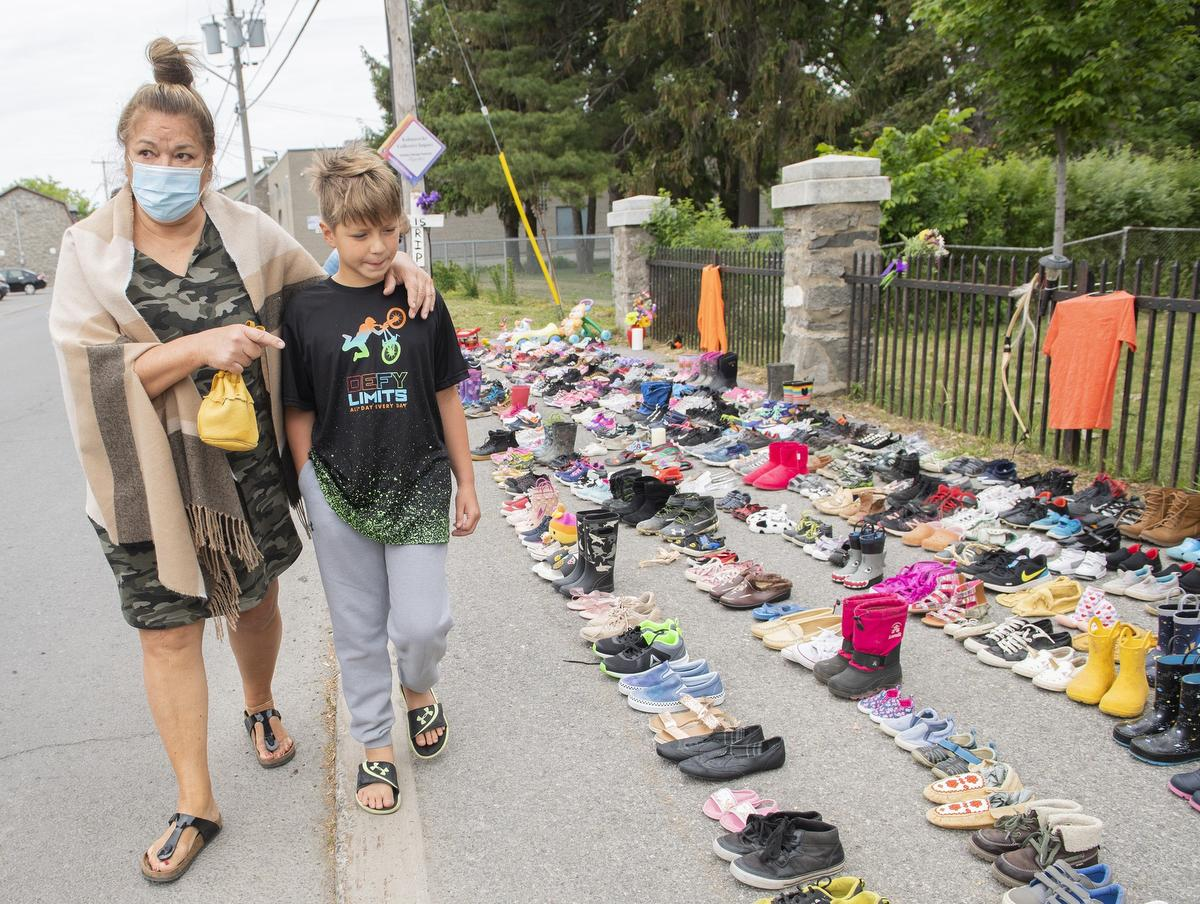 Lynn Karonhia-Beauvais and grandson Jamieson Kane put down tobacco as a tribute to victims of the residential school system as they walk next to children's shoes outside St. Francis Xavier Church in Kahnawake, Que.